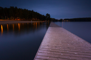 Landscape with wooden jetty on city beach of Olsztyn in Poland. Long exposure landscape with architecture elements.