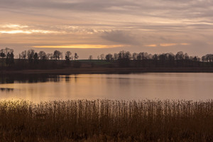 Sunset sky over autumnal lake. Polish landscape with beautiful evening sky.