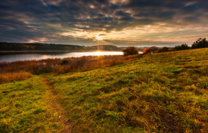 Beautiful autumnal landscape of lake and and colorful plants photographed at sunset. Amazing dreamy landscape.