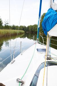 Beutiful Mazury lake photographed from yacht.-Front part of yacht swimming on lake.