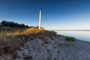 Surfing board on Baltic sea shore in Gdanska bay. Beautiful morning landscape