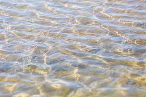 Abstract background of ripples on water surface on sea shore. Beautiful natural abstract background