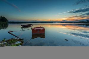 Beautiful lake sunset with fisherman boats. Polish lake in Mazury lake district. Polish lake landscape--