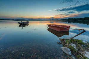 Beautiful lake sunset with fisherman boats. Polish lake in Mazury lake district. Polish lake landscape