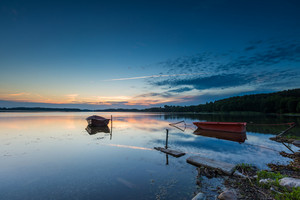 Fisherman boats moored on lake shore under sunset sky. Beautiful lake in Mazury lake district in Poland.