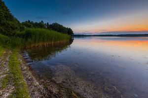 Beautiful lake at sunset landscape with cloudy sky reflecting in water. Polish lake in Mazury lake district