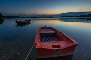 Beautiful lake sunset with fisherman boats. Polish lake in Mazury lake district. Polish lake landscape