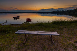 Beautiful lake sunset with fisherman boats and bench on shore. Polish lake in Mazury lake district. Polish lake landscape--