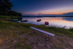 Beautiful lake sunset with fisherman boats and bench on shore. Polish lake in Mazury lake district. Polish lake landscape--