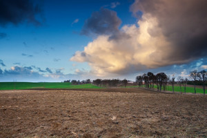 Dramatic sunset sky with clouds over rural field in Poland