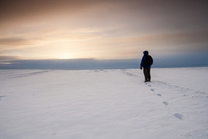 Snow field landscape with man standing and looking on sunset