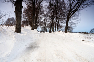Asphalt road in countryside covered by snow