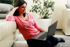 Middle-aged happy woman sitting on the floor and using laptop at home