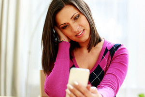 Middle-aged thoughtful woman holding smartphone and looking on it