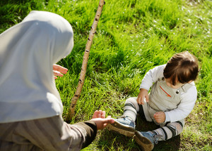 Middle Eastern Muslim mother playing with her little baby in the garden planting the new tree