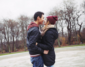 Mixed race teenage couple about to have a passionate kiss in park. Handsome young man and beautiful young woman in warm clothes together.