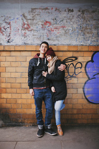 Mixed race teenage couple in lover embracing each other while standing against a wall. Romantic young couple outdoors.