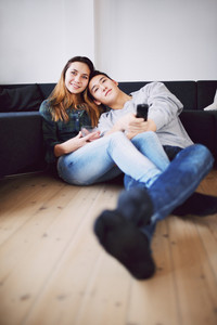 Mixed race teenage guy holding remote control relaxing with his beautiful girlfriend at home. Loving young couple sitting together on floor watching TV.