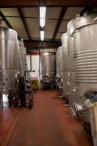 Modern aluminum storage tanks where grape juice is aged into wine located in a vineyard cellar.
