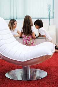 Modern furniture in home, white leather chair, family in background