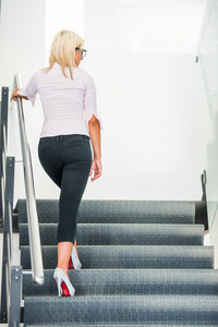 Modern handsome blonde woman climbing stairs