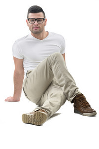 Modern looking male model sitting on the floor isolated on white