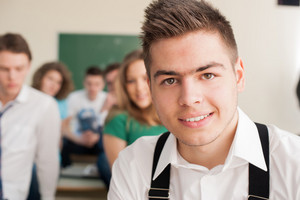 Modern looking student posing in front of his classroom
