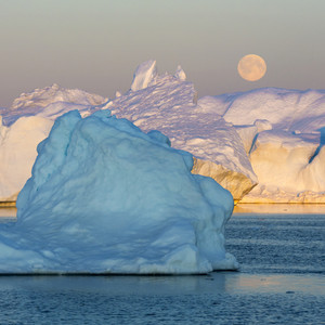 Moonlit icebergs against a full moon