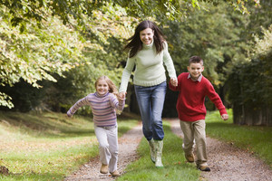 Mother and children running along woodland path in autumn