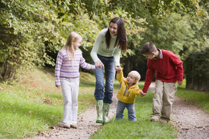 Mother and children walking along woodland path in autumn