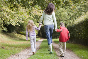 Mother and children walking on woodland path in autumn
