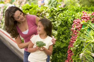 Mother and daughter choosing fresh produce in supermarket