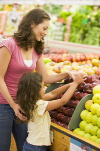 Mother and daughter in produce section of supermarket