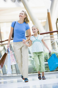 Mother and daughter in shopping mall carrying bags