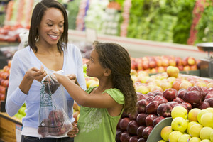 Mother and daughter in supermarket produce section