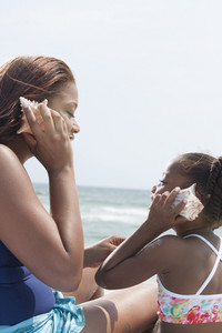 Mother and daughter listening to seashells