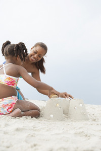 Mother and daughter making sand castle at the beach