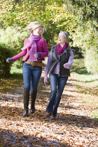 Mother and daughter on walk through autumn woods
