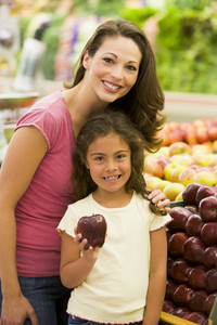Mother and daughter shopping for fresh produce in supermarket