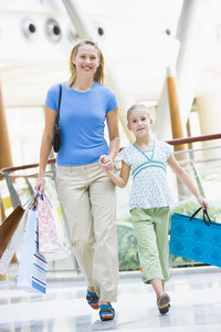 Mother and daughter shopping in mall carrying bags