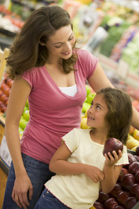 Mother and daughter shopping in produce section of supermarket