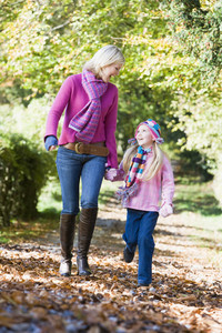 Mother and daughter walking along autumn path through trees