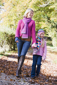 Mother and daughter walking along woodland path in autumn