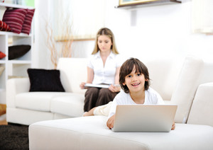 Mother and her kid having god time together using laptop at home on couch