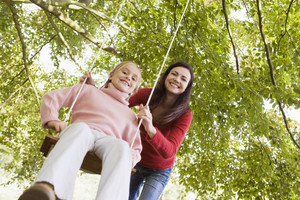 Mother pushing daughter on garden swing