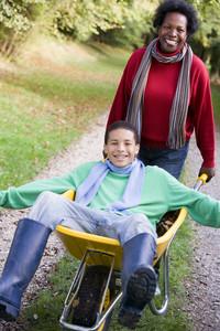 Mother pushing teenage son laying in wheelbarrow