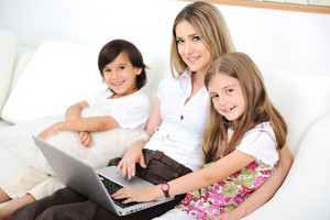 Mother with daugther and son using  laptop on sofa indoor