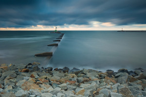 Mouth of the river Vistula in Gdansk. Long exposure seascape. Beautiful rocky breakwater on sea shore and protection walls on mouth of river.