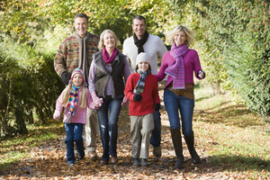 Multi-generation family on walk through autumn woods