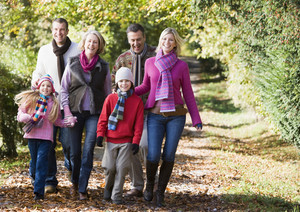 Multi-generation family walking through autumn woods